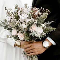 Apsveikuma e-kartiņa Līgava un līgavainis tur kāzu puķu pušķi
