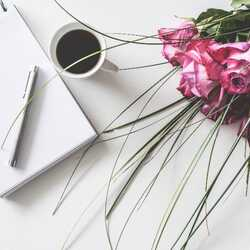 Greeting e-card Red roses next to a notebook and a cup of coffee