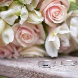 Apsveikuma e-kartiņa Sudraba kāzu gredzeni uz puķu pušķa fona
