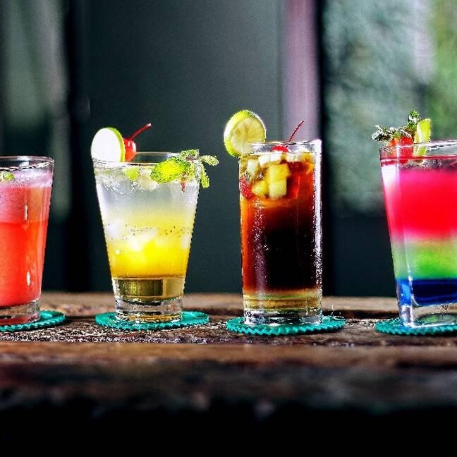 Četras krāsainas alkohola glāzes uz galda e-kartiņa