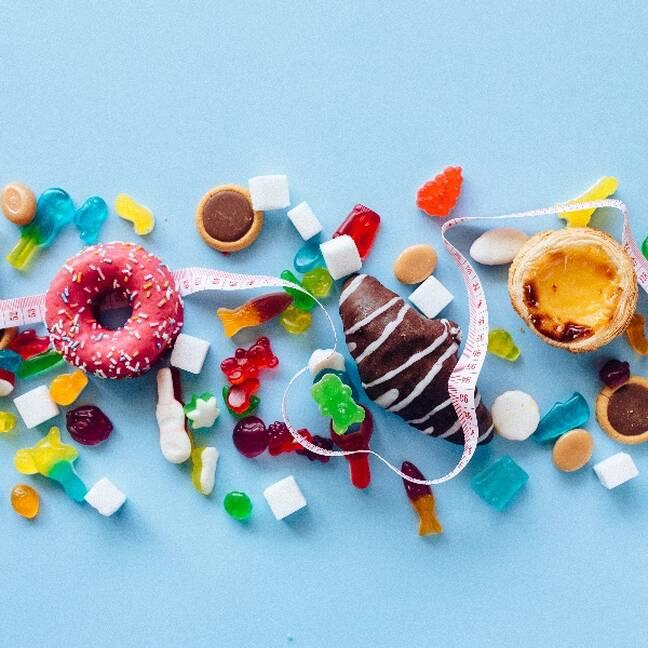 Dažādi saldumi ar metramēru uz zila fona e-kartiņa