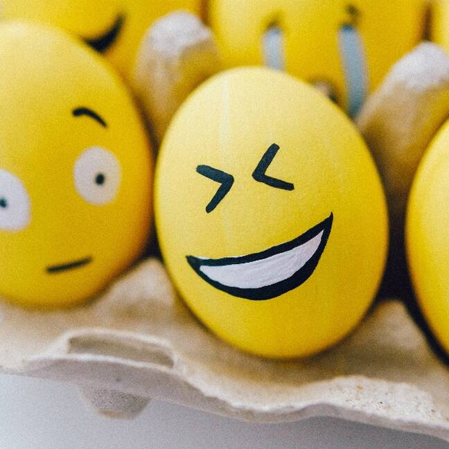 Close-up of yellow eggs with different facial expressions e-card