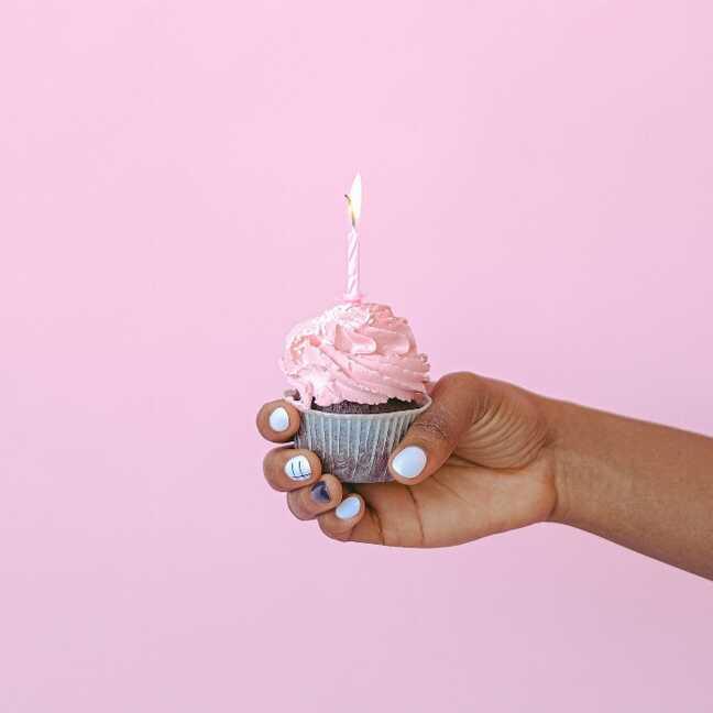 Dzimšanas dienas kūciņa rokā ar iedegtu svecīti e-kartiņa