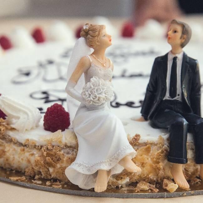 Kāzu tortes tuvplāns ar līgavas un līgavaiņa figūriņām e-kartiņa