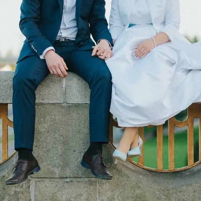 Līgavainis un līgava sēž sadevušies rokās e-kartiņa