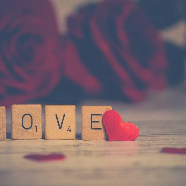 Love uzraksts uz koka klucīšiem ar rozēm fonā e-kartiņa