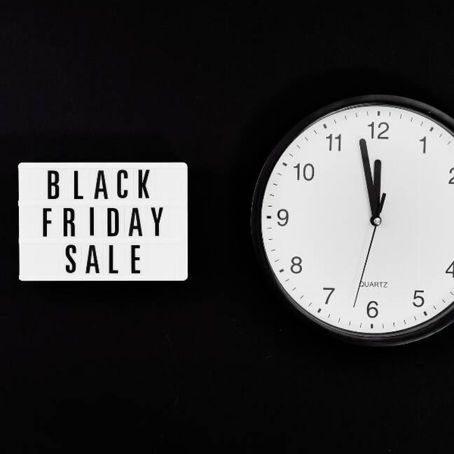 Melnās piekdienas izpārdošana uzraksts uz melna fona ar pulksteni e-kartiņa