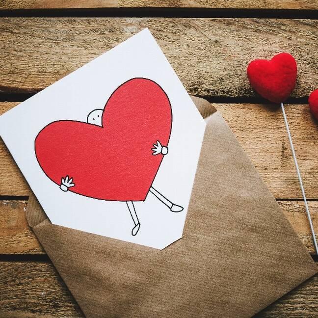 Melnbalta persona tur sarkanu sirdi zīmējums konvertā blakus sirdīm e-kartiņa