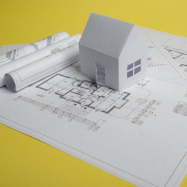 Papīra mājiņa un mājas plāns uz dzeltena galda e-kartiņa