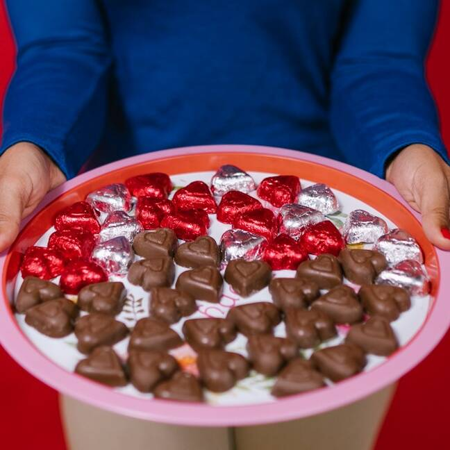 Persona tur paplāti ar sirdsveida šokolādes konfektēm e-kartiņa