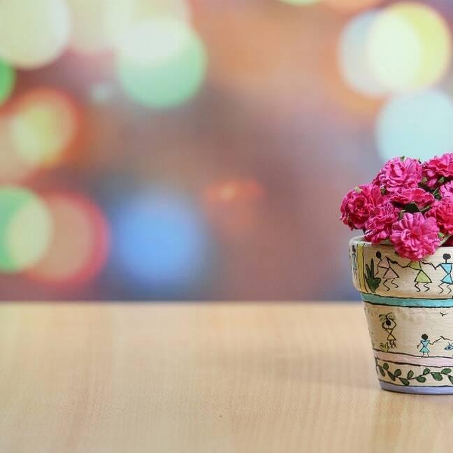 Rozā puķes podiņā uz galda e-kartiņa
