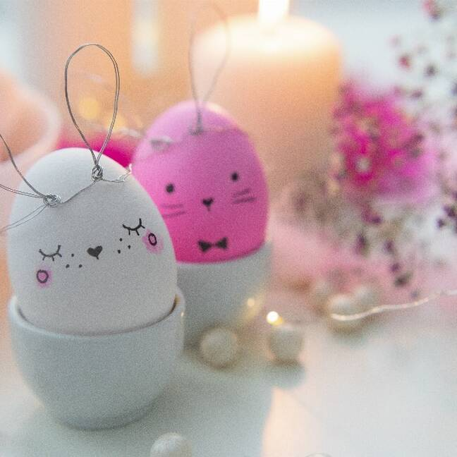 Pink and white egg with eyes next to a candle e-card