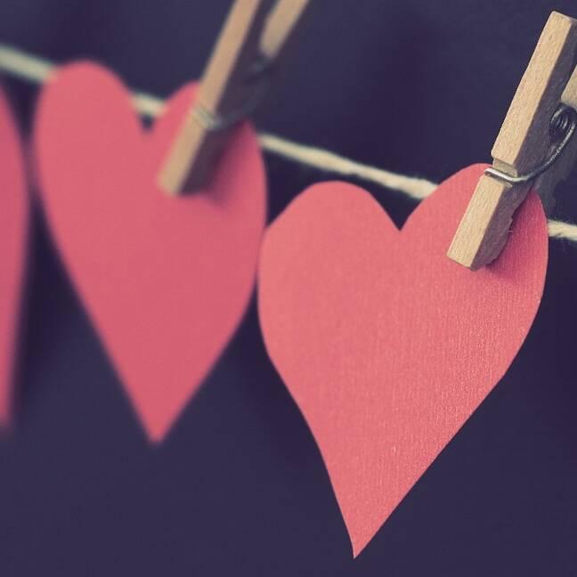 Sarkanas sirds formas papīri karājās uz striķa e-kartiņa