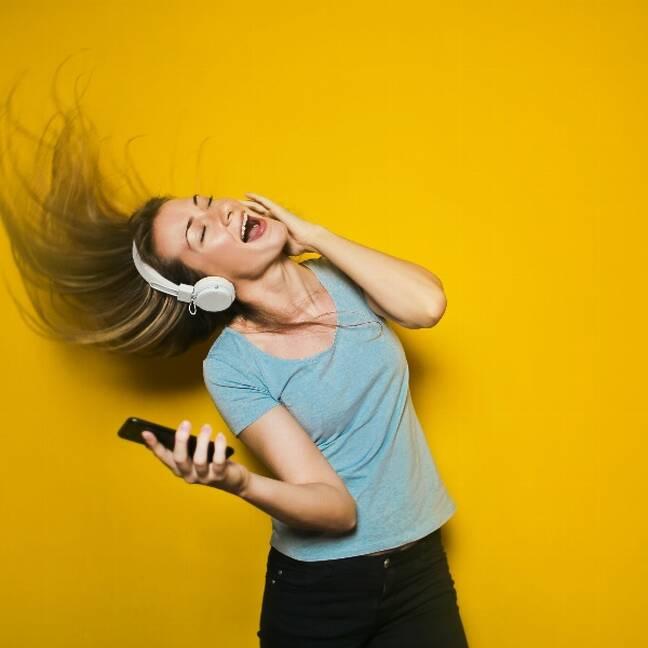Sieviete dzied klausoties mūziku uz austiņām e-kartiņa