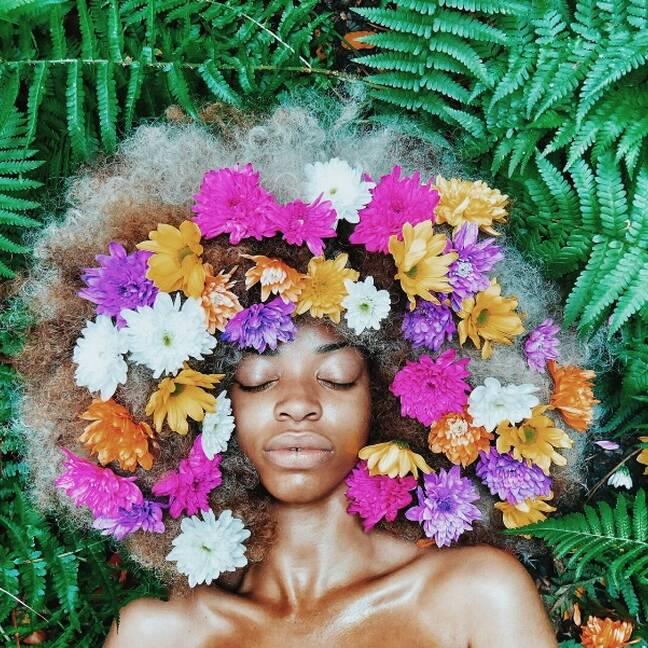 Sieviete starp papardēm ar ziediem matos e-kartiņa