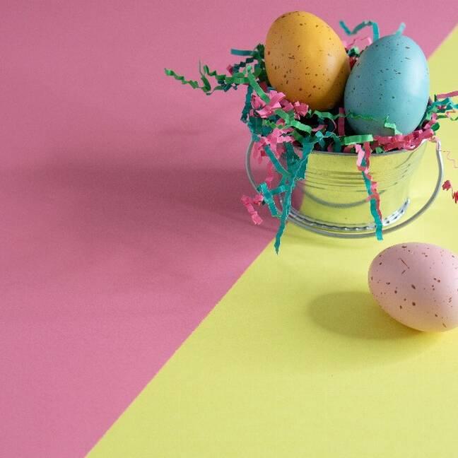 Trīs krāsu lieldienas olas uz rozā dzeltena fona e-kartiņa